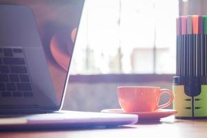 bärbar dator med kaffe och pennor foto
