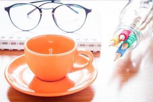 närbild av en kaffekopp med glasögon och pennor