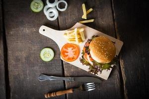 ovanifrån av rustik hemlagad hamburgare och pommes frites foto
