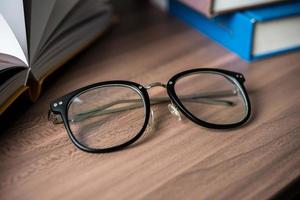 glasögon på ett träbord med böcker foto