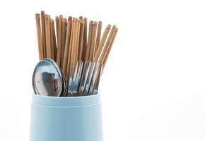 bestickhållare med ätpinnar, sked och gaffel på vit bakgrund