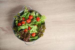 färsk sallad med grönsaker och gröna på träbord foto