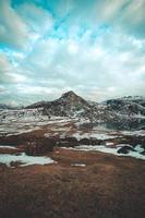 vidvinkel skott av en frusen sjö framför ett snöat berg foto