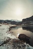 bergskedja som reflekterar i en frusen sjö