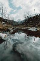 berg som reflekterar i vattnet foto