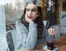 vacker ung kvinna som dricker te i ett kafé. foto