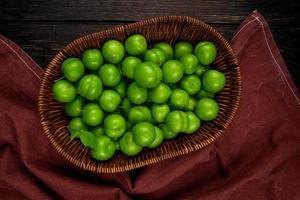 korg med sura gröna plommon på en mörk rustik bakgrund