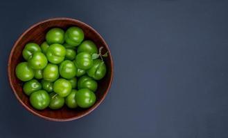 sura gröna plommon i en träskål på svart bakgrund med kopieringsutrymme