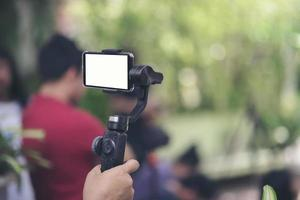 hand som håller gimbal med smartphone foto