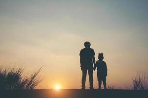silhuett av far och son står tillsammans foto