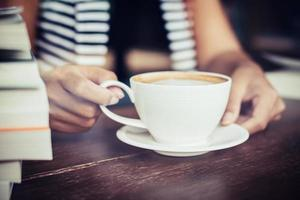 kvinnans händer som kopplar av med kaffe på kaféet