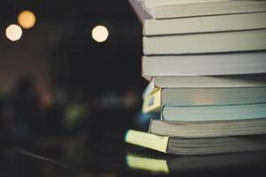 högar med böcker på ett bord över en suddig biblioteksbakgrund