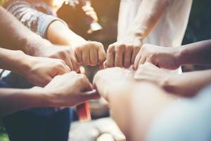 närbild av ungdomar som sätter ihop händerna