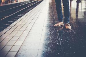 fötter på en ung man som bär jeans som väntar på tåget foto