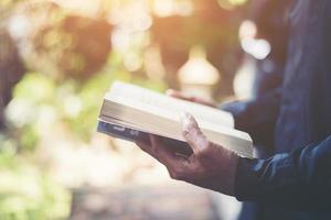 man som läser en bok i hans händer