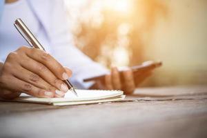 kvinna skriver i anteckningsboken foto