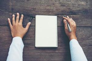 manhandstil på tom anteckningsbok på träbord foto
