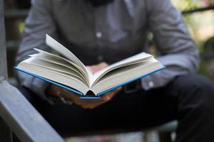 ung man läser böcker i hemträdgård med naturen