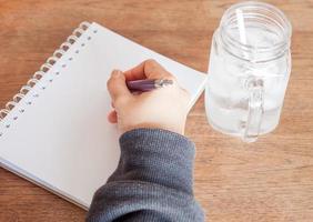 närbild av en person som skriver i en anteckningsbok med ett glas vatten