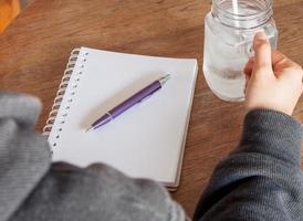 anteckningsbok och penna med ett glas vatten på ett bord