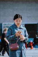 kvinna som går med sin telefon foto
