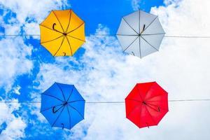 fyra paraplyer i olika färger hängda på kabel under molnig himmel