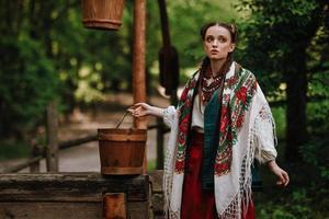flicka i en traditionell etnisk klänning poserar vid brunnen foto