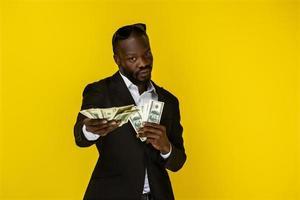 svart man som håller mycket pengar
