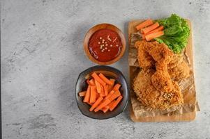 krispiga stekt kyckling och morotpinnar med sås foto