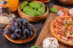 svarta druvor med tomater apelsinjuice och pizza foto