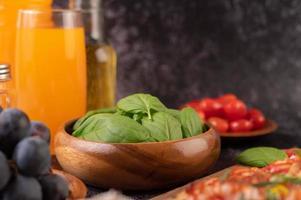timjan och tomater i en träkopp med vitlök foto