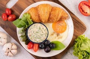 croissant, stekt ägg, salladsdressing, svarta druvor och tomater