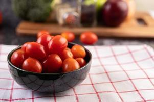 färska mogna tomater på en röd rutig trasa foto