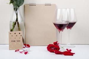 glas vin med en anteckningsbok och ett kort foto