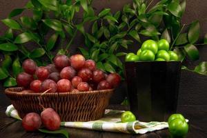 röda druvor och sura plommon i skålar foto