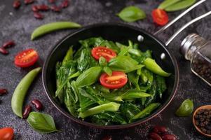 rörstekt grönkål i en kastrull med tomater och paprika