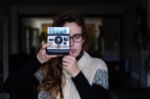 flicka som använder en polaroidkamera