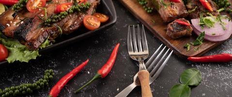 två gafflar med chili och kaffirlime på svart bakgrund foto