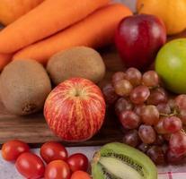 närbild av äpplen, druvor, morötter och apelsiner foto