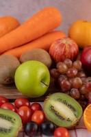 närbild av kiwi, druvor, äpplen, morötter och tomater foto