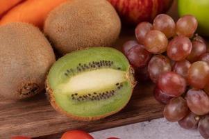 närbild av kiwi, druvor, äpplen, med morötter foto