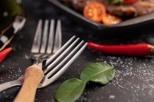 två gafflar med chili och kaffir lime blad på en svart bakgrund foto