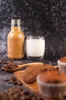 kaffe och mjölk med muffins och kaffebönor i förgrunden