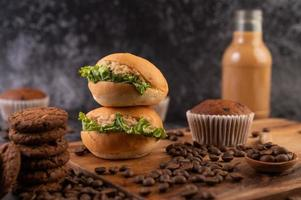 hamburgare på en skärbräda, med muffins och kaffebönor