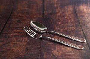 rostfri gaffel och sked på ett träbord foto