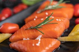 rå laxfilé med peppar, kiwi, ananas och rosmarin foto