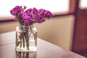 lila blommor i en glasburk
