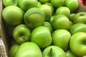 låda med gröna äpplen foto