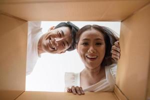lyckligt par som öppnar en låda och tittar inuti foto