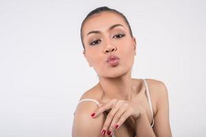 porträtt av en ung kvinna puckar läppar på kameran